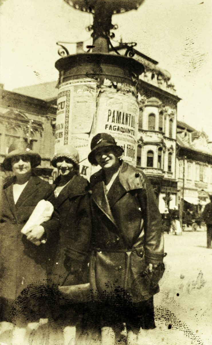 Hölgyek Marosvásárhely főterén az impériumváltás éveiben. A háttérben látható hirdetőoszlopon jól láthatók a kétnyelvű plakátok   Forrás: Fortepan